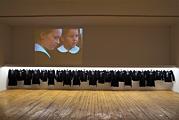 Ich bin Türke, bin ehrlich, bin fleissig?, 2005, Installationsansicht mit 21 türkischen Schuluniformen im O.K Centrum für Gegenwartskunst, Linz, Foto: Otto Saxinger Von Montag bis Freitag notierten die Kinder jeweils, wie ihnen der Auftritt in der Schuluniform gefallen hat. Am Ende des Projekts wurden die tagebuchartigen Notizen per Siebdruck auf die Uniformen appliziert.