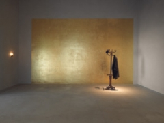 Jannis Kounellis · Tragedia civile, 1975, Blattvergoldete Wand, Garderobenständer, Hut, Mantel, Öllampe. Foto: Lothar Schnepf