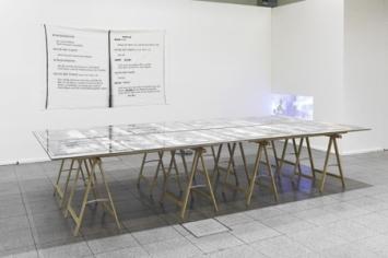 Theater der Umgesiedelten Mixed Media: Tisch 180×380 cm, MDF, Glas, Fotos/ Banner: 150×250 cm, Digitaldruck auf Leinen/Projektion: 47×70 cm, HD-Film, 40', Loop, 2012