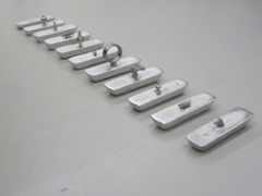 Ilona Rüegg · Option 2013, 11 gegossene Zinnbarren, 10 verschiedene Deckelfiguren, von eingeschmolzenen Zinnkrügen, je ca. 5x24x7 cm