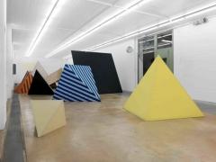 Sonia Kacem · Loulou, 2014, 10 pyramidenförmige Gerüste aus Metall, 17 pyramidenförmige Gerüste aus Holz, Bezüge aus unterschiedlichen Textilien, Grösse variabel, Installationsansicht MAMCO Genf. Foto: Annick Wetter