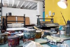 Atelierhaus Wolfensberger, Durchgang zum Ätzraum in der Kupferdruckwerkstatt und die über 100-jährige Schnelldruckpresse in der Steindruckerei.
