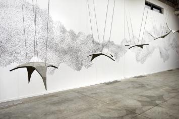 Marco Godinho · Forever Immigrant, 2012, Wandzeichnung; im Vordergrund: Hector Zamora, Synclastic/ Anticlastic, 2012, Ausstellungsansicht Biennale de Lyon, Sucrière. Foto: Blaise Adilon