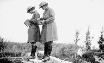 Anonym · Mairi Chisholm und Elsie Knocker mit Stahlhelmen, während sie ihre Kameras kontrollieren, vermutlich in Pervijze, Belgien, 1917 Courtesy Imperial War Museum