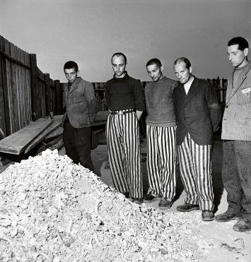 Lee Miller · Released prisoners in striped prison dress beside a heap of bones from bodies burned in the crematorium, KZ Buchenwald, 1945, Schwarzweissfotografie, Courtesy Lee Miller Archives England