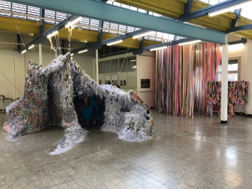 ‹Elles disent qu'elles sont peintres›, Trélex Esp'asse Residency, Fondation Esp'Asse, Nyon, 2019, im Vordergrund Laura McGlinchey, ‹The Nature of the Beast›, 2009, Papiere, Schnüren, Mehle, Acrylfarbe, 3.4 x 6.4 x4.3 m, im Hintergrund Nina Rodin, ‹Ohne Titel (Werkreihe in Arbeit)›, 2017-2019, Plastikstreifen, Performance, Foto, Video, Dimensionen variabel.Foto: Katharina Holderegger