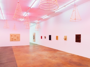 Mai-Thu Perret · Sans titre, 2015, 9 néons, H 100cm; Ø 65cm, court. Galerie VNH, Paris, sur les murs: céramiques émaillées, 2007–2017.Photo: Annik Wetter
