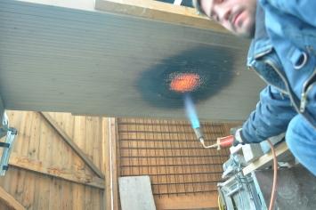 Kilian Rüthemann,Bearbeitung der Holzlamellen für den Aussenbereich über dem Eingang