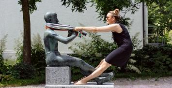 Andrea Vogel · Aktion mit Frotteetuch und Sitzender Klarinettist, Skulptur von Ernst Heller, Jakob-Züllig-Park, Arbon, 20.6.2021. Foto: Stefan Rohner