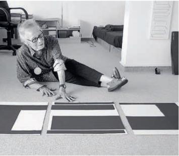 Auf dem Boden ihres Studios sitzend, erklärt die 95-jährige Vera Molnar den Algorithmus eines ihrer Gemälde, Courtesy Galerie La Ligne