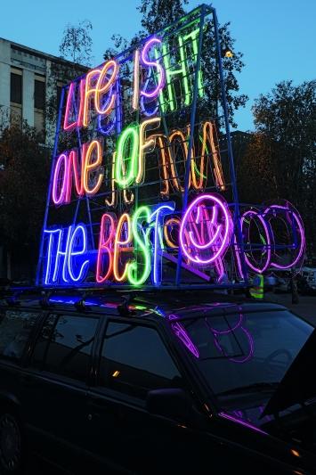 Veli & Amos,LIFE IS ONE OF THE BEST, THIS IS NOT A COMMERCIAL, 2019, Turbinenplatz, Zürich. (Plakatwand, Neonschrift, Soundsystem, Gebrauchtwagen)© Cédric Eisenring / Kunst im öffentlichen Raum Zürich («Gasträume 2019»)Courtesy: die Künstler und oncurating, Zürich
