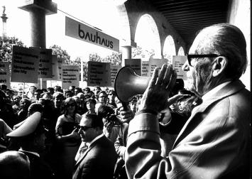 Walter Gropius am Tag der Ausstellungseröffnung. Er richtet sich mit einem Megafon an die Demonstant*innen, Schwarz-Weiss-Fotografie, Courtesy: WKV Archiv. Foto: Kurt Eppler